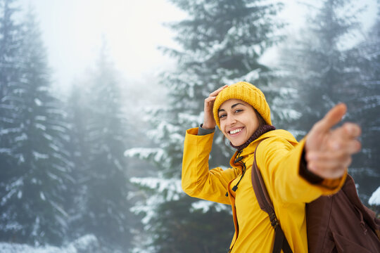 portrait traveler woman in bright yellow warm clothing at winter foggy forest giving hand to camera like follow me