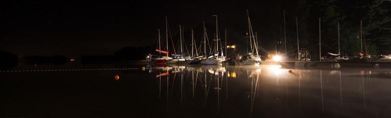 Oświetlone jachty przycumowane do pomostu nad jeziorem