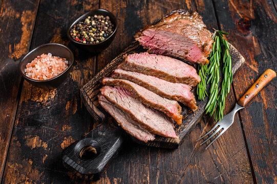 Sliced Roast beef sirloin tri tip steak bbq. Dark wooden background. Top view
