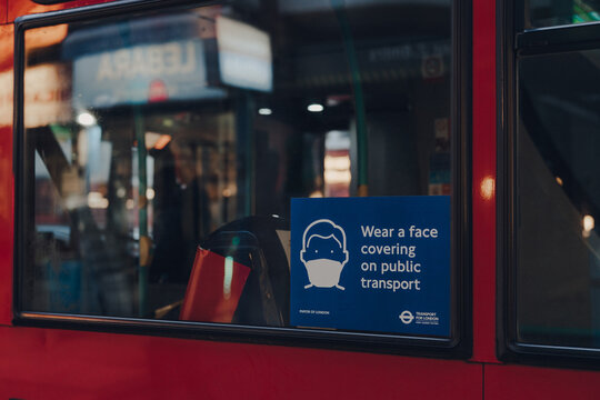 London, UK - December 5, 2020: Wear a face mask sign on the window of a red double decker bus in London, UK.