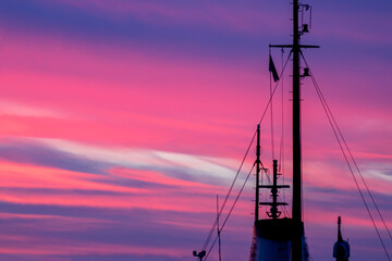 A detail photo of ship's silhouette mast at sunset with blue and pink sky with landscape frame