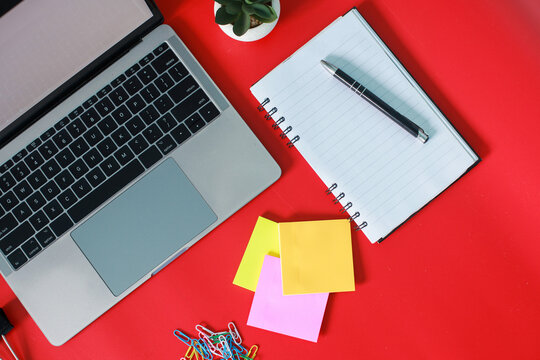Flat lay top view of stylish home office with laptop, book, sticky note and accessories isolated on red background