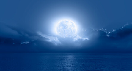 "Night sky with moon in the clouds on the foreground blue sea ""Elements of this image furnished by NASA"