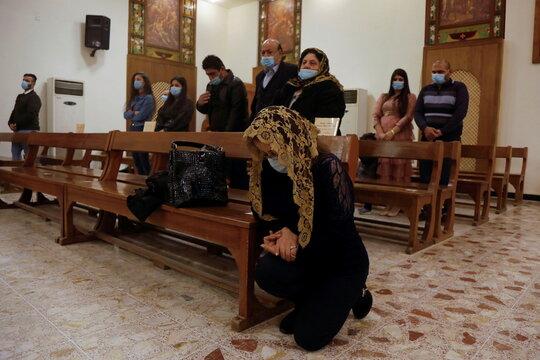 A Christian woman prays during a mass on Christmas at St. Elya Chaldean Church in Baghdad