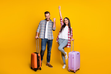 Photo portrait full body view of cheerful excited couple with suitcases isolated on vivid yellow colored background