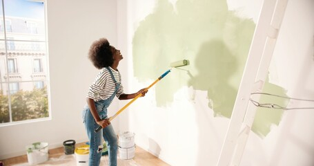 Obraz Young African American woman dancing and painting wall with roller brush while renovating apartment. Rear of female having fun redecorating home, renovating and improving Repair and decorating concept - fototapety do salonu