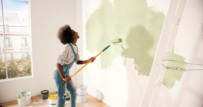 Young African American woman dancing and painting wall with roller brush while renovating apartment. Rear of female having fun redecorating home, renovating and improving Repair and decorating concept