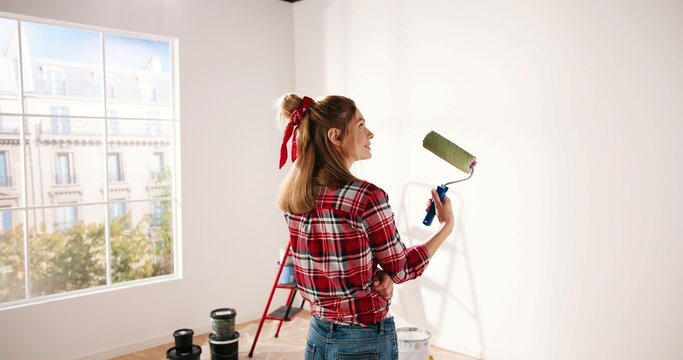 Close up. Side view of pretty joyful Caucasian woman alone painting room in new house in green color. Beautiful female renovating home painting wall using roller brush redesigning apartment