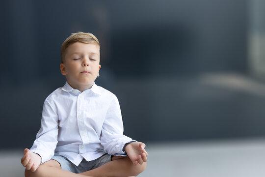 Zen-like boy meditating with eyes closed.