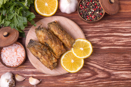 Pieces of fried carp on a wooden board with herbs, spices and lemon. Top view