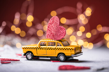 Red heart on toy yellow  taxi car on red background. Travel love concept with copy space.