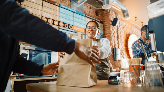 Beautiful Happy Latin Barista Serves Order to a Food Delivery Courier Picking Up Paper Bag with Pastries from a Cafe Restaurant. Delivery Guy Puts Food in His Hot Thermal Insulated Bag.