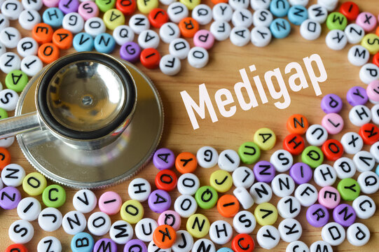 Selective focus of colorful alphabet beads and stethoscope over wooden background written with text MEDIGAP. Health concept.