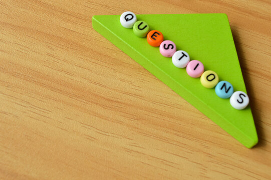 Selective focus with blurred effect of wooden blocks and colorful alphabet beads with text QUESTIONS. Business and education concept.