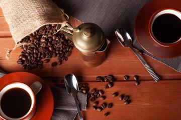 Mesa tradicional con tazas y granos de café saliendo de una bolsa.