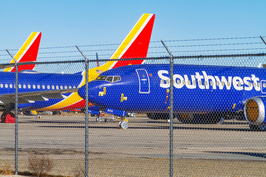 Victorville, CA, USA – December 22, 2020: Behind a chain link fence, Southwest Airlines airplanes remain at the Southern California Logistics Airport in Victorville, California.