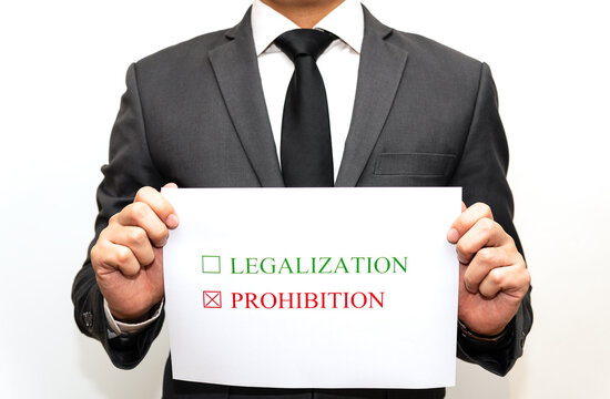 Concept of judge or lawmaker: the paper with the words legalization and prohibition is placed with justice scales and wooden gaven. The hand is going to choose whether to legalize or prohibit.