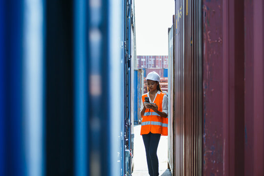 Young business woman or Cargo container woman container then use barcode scanner check the product and using tablet to monitor inventory while working in the container depot. for import and export