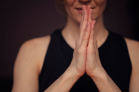 middle aged woman meditating with her eyes closed, practicing Yoga with hands in prayer position.