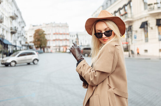 Portrait of young stylish blonde woman in autumn coat, sunglasses and felt hat wear gloves in European city. Beautiful attractive girl