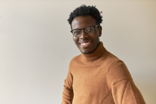 Isolated image of attractive stylish young African American man in trendy glasses looking at camera with broad smile, expressing joy, being happy to get new prospective job with good salary
