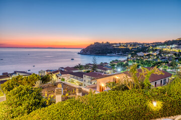 View at the summer sunset of the houses and the touristic resorts along the shores of Capo Vaticano, Southern Italy, Calabria Region. It's located along the Tyrrhenian Sea coastline. Fotobehang