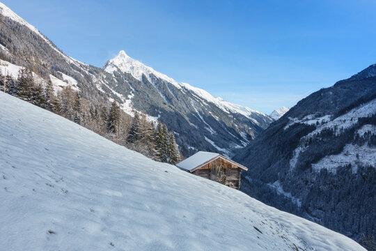 Berghütte mit verschneitem Berggipfel im Hintergrund