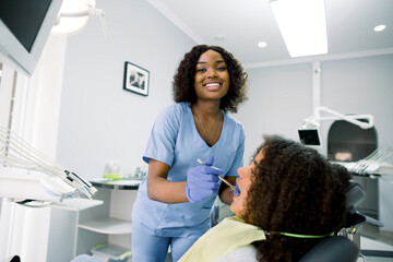 Side view of happy pretty african lady dentist in blue uniform and gloves, making examination or...