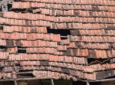 Old worn out red brick roof with missing tiles