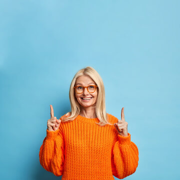 Pretty blonde forty years old woman smiles happily indicates at copy space recommends something says check out this promo wears spectacles orange sweater isolated over blue background. Advert concept