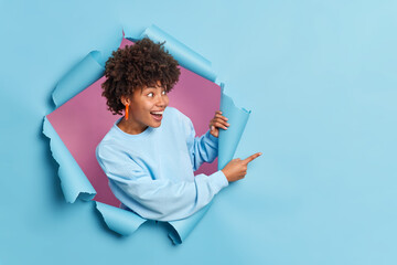 Obraz Cheerful dark skinned woman with curly hair dressed in casual sweater indicates at copy space shows amazing offer breaks through paper background expresses positive emotions. Your advertisement there - fototapety do salonu
