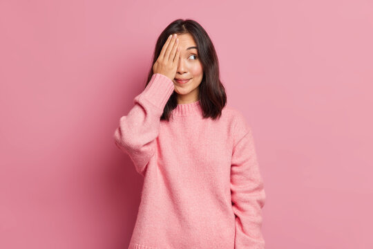 Beautiful brunette young Asian woman with eastern appearance covers eyes with hand hides face smiles pleasantly wears casual knitted sweater poses against rosy background. Dont look at me please