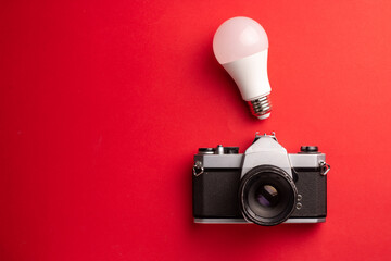 A top view of a light bulb and a camera on a red background