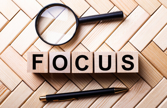 Wooden cubes with the word FOCUS stand on a wooden background between a magnifying glass and a handle