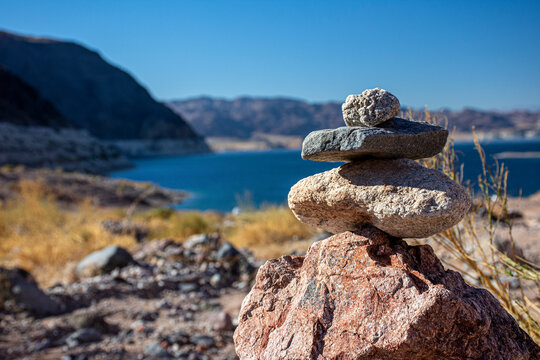 Rock Cairn at Desert Lake - stones stacked on top of each other acting as natural marker and guide for hikers