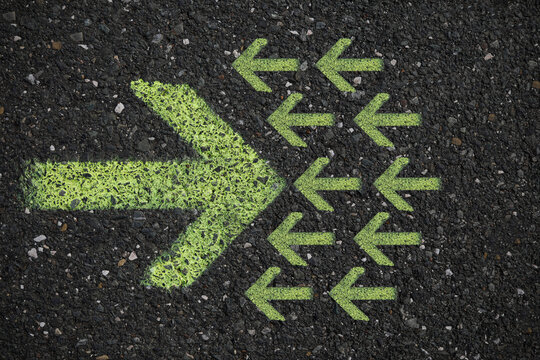 Green arrows on a dark asphalt road, road sign for information, go ahead for new ideas, space for text