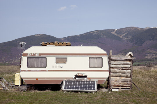 An old trailer permanently set at a field with a mountain in the background