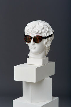 Plaster head of Antinous with round glasses. The concept of the absurd and the combination of the incongruous
