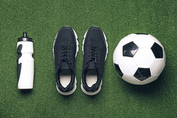 Sportive shoes, soccer ball and bottle of water on color background