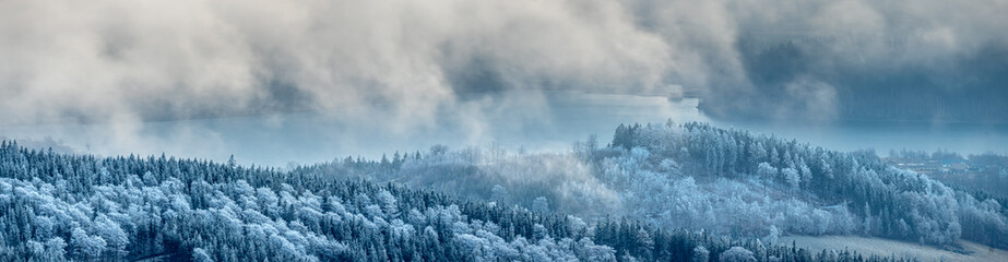 panorama of the mountain landscape in winter over which heavy snow clouds are flowing