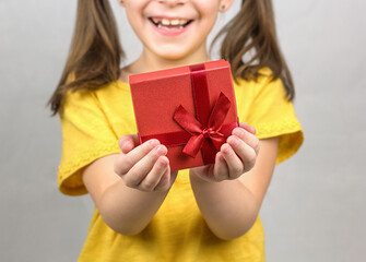 Smiling girl holding red present box with ribbon bow in her hands