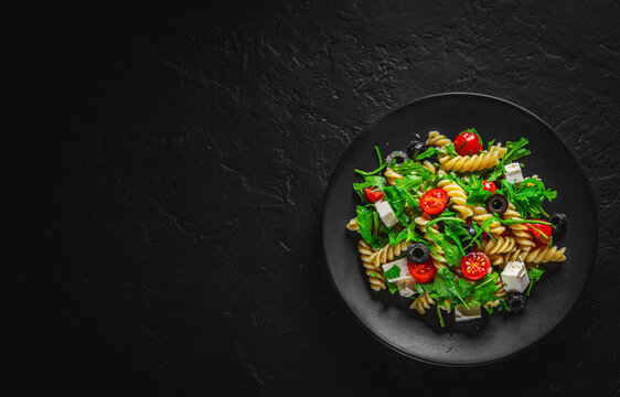 Salad with pasta, arugula, tomato, cheese and olives on black plate on Dark grey black slate background