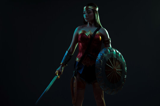 Ancient woman warrior stands with sword and shield in her hands.