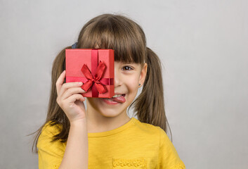 Photo of attractive little girl long straight ponytails holds in a hand a red present box with ribbon bow. Happy girl with gift shows her tongue and smiles
