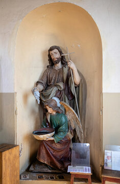 Statue of John the Baptist on the wall of the Church of Holy Trinity in Suderve, Lithuania