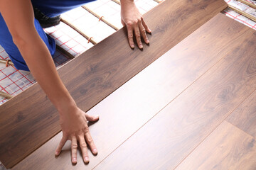 Worker installing new wooden laminate over underfloor heating system, closeup