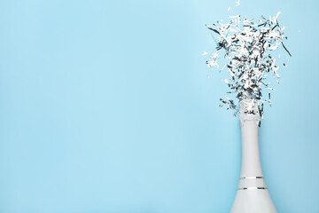 Flat lay composition with confetti and bottle of champagne on light blue background. Space for text