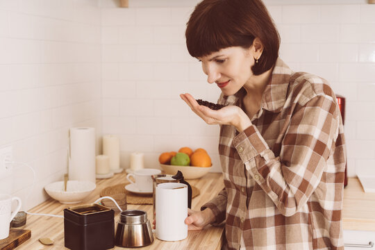 Anosmia, restore sense of smell. COVID-19 causes loss of smell. Happy woman sniffing coffee from hand and smelling aroma. Female inhaling fresh beans. SARS-CoV-2 pandemic.
