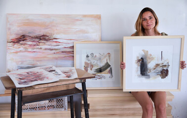 Modern art and lifestyle. Female artist showing her work in the studio. Portrait of young adult...