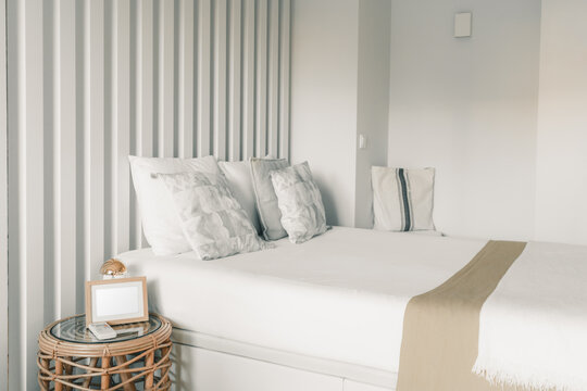 A bright white neatly made bed in a bedroom of a residential apartment of a hotel room with pillows and cushions on the top and a small nightstand with a blank white template of a picture frame on it